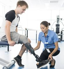 Physiotherapist attending to young man's prosthetic leg